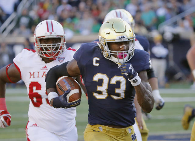 "Notre Dame running back <a class=""link rapid-noclick-resp"" href=""/ncaaf/players/257306/"" data-ylk=""slk:Josh Adams"">Josh Adams</a> (33) rushed for 1,430 yards this season (AP Photo/Charles Rex Arbogast)"