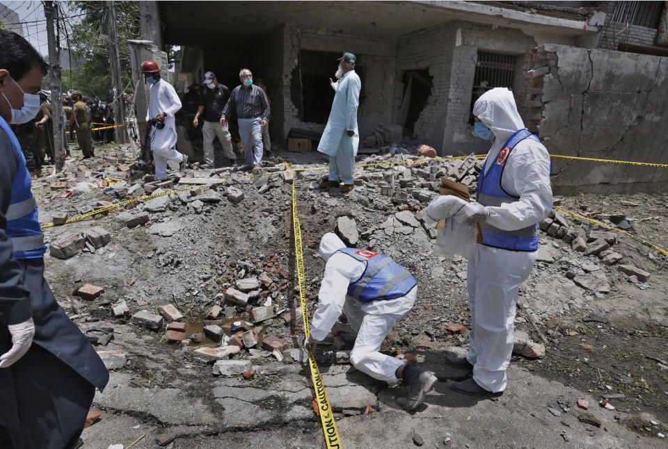 Investigators collect evidence at the site of explosion in Lahore, Pakistan, Wednesday, June 23, 2021. A powerful explosion ripped through a residential area in the eastern city of Lahore on Wednesday, killing few people and injuring some others, police and rescue officials said. (AP Photo/K.M. Chaudary)