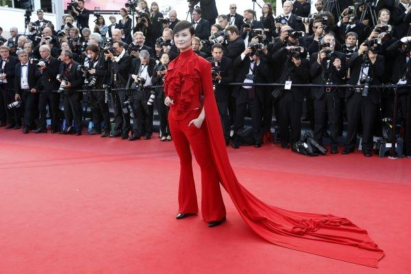 """Li Yuchun The Chinese singer and actress forgot that wearing red on the red carpet is a bit redundant! This Gareth Pugh suit looked very nice though, highlighting her androgynous figure. She was on her way to the screening of """"Behind the Candelabra""""."""