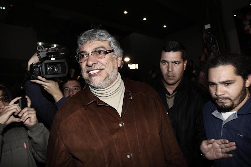 """Paraguay's former President Fernando Lugo smiles after talking to his followers gathered outside the Public Television building in downtown Asuncion, Paraguay, in the early hours of Sunday, June 24, 2012. Lugo spoke in a pre-dawn special televised """"open microphone"""" program hosted by the state-funded Public Television channel that was created by his government, to denounce his ouster as a """"parliamentary coup"""". (AP Photo)"""