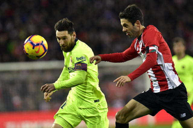 FC Barcelona's Lionel Messi, left, duels for the ball beside Athletic Bilbao's Markel Susaeta during the Spanish La Liga soccer match between Athletic Bilbao and FC Barcelona at San Mames stadium, in Bilbao, northern Spain, Sunday, Feb. 10, 2019.(AP Photo/Alvaro Barrientos)
