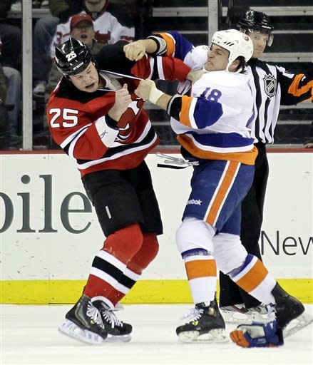 New Jersey Devils' Cam Janssen (25) and New York Islanders' Micheal Haley (18) fight in the first period of an NHL hockey game Tuesday, April 3, 2012, in Newark, N.J. (AP Photo/Julio Cortez)