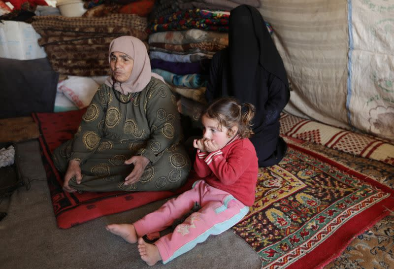 Aziza Hadaja, an internally displaced woman, sits with her relatives inside a tent near the town of Afrin