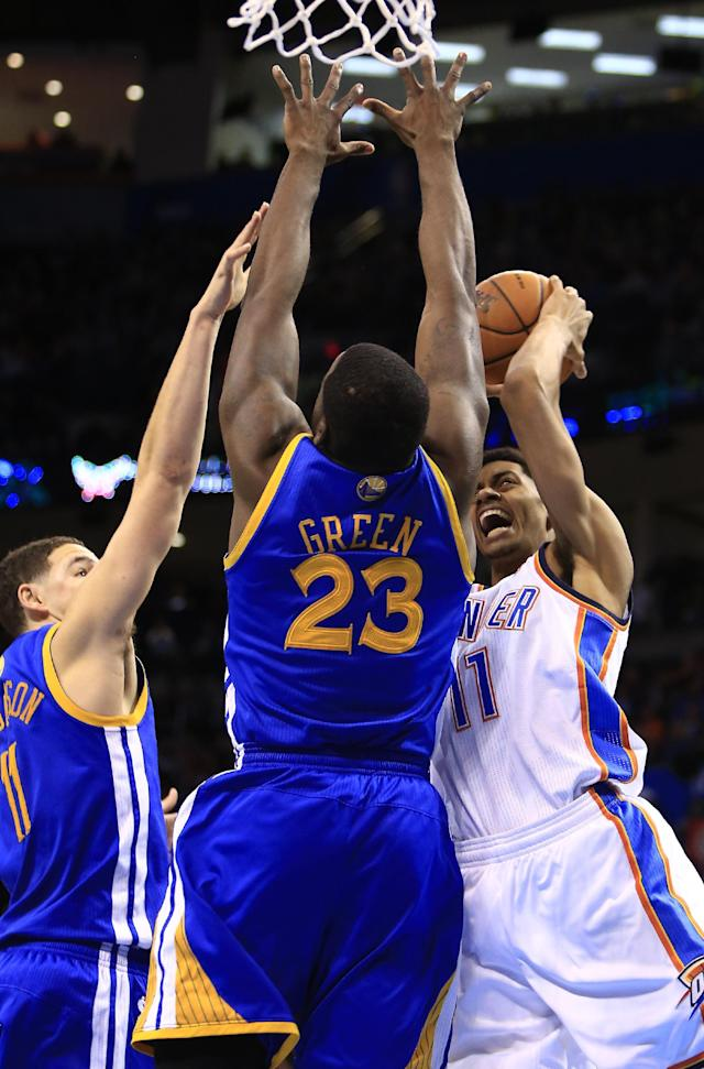 Oklahoma City Thunder shooting guard Jeremy Lamb (11) shoots as Golden State Warriors small forward Draymond Green (23) and Golden State Warriors shooting guard Klay Thompson (11) defend during the fourth quarter of an NBA basketball game Friday, Jan. 17, 2014, in Oklahoma City. (AP Photo/Alonzo Adams)
