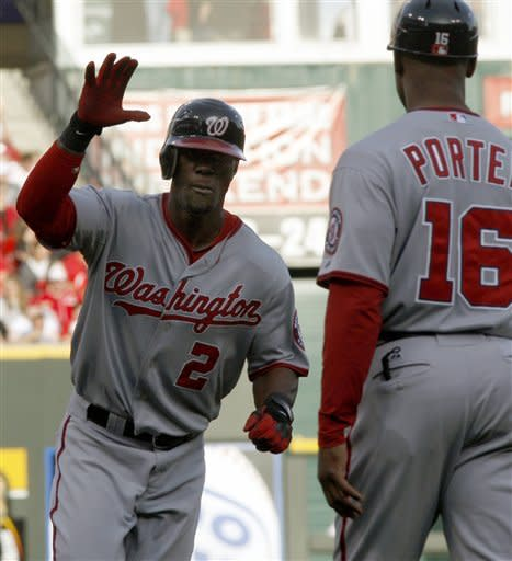Washington Nationals' Roger Bernadina (2) heads torward home plate past third base coach Bo Porter (16) after hitting a two-run home run off Cincinnati Reds starting pitcher Mike Leake during the first inning on Friday, May 11, 2012, in Cincinnati. (AP Photo/David Kohl)