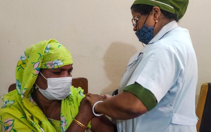 A sex worker from Bangladesh's largest brothel receives a dose of a Covid-19 vaccine in Daulatdia - AFP