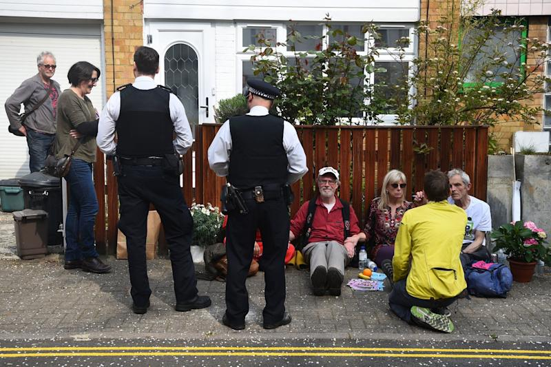Police officers talk with climate activist who have glued themselves together outside Labour Party leader Jeremy Corbyn's house in north London (PA)