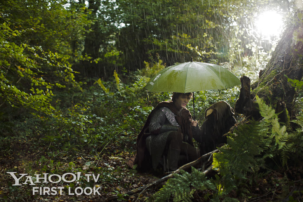 Actor Alexander Vlahos, as Mordred, waits for a rain shower to pass on location in Wales.