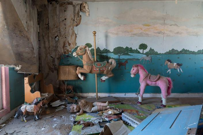 The interior of an abandoned house with toy horses.