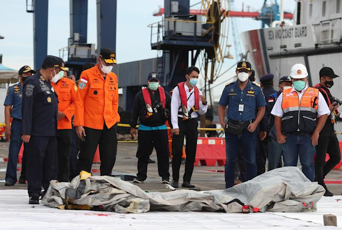 Searchers inspect debris found in the waters near where a Sriwijaya Air passenger jet lost contact with air traffic controllers shortly after takeoff.