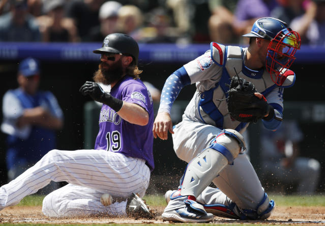 Los Angeles Dodgers catcher Yasmani Grandal, front, misses the throw as Colorado Rockies' Charlie Blackmon scores on a sacrifice fly hit by Trevor Story in the first inning of a baseball game Sunday, Aug. 12, 2018, in Denver. (AP Photo/David Zalubowski)
