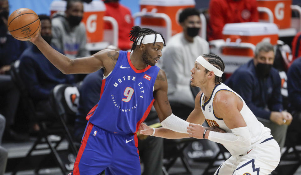 Detroit Pistons forward Jerami Grant (9) holds the ball away from Denver Nuggets forward Aaron Gordon (50) in the first quarter of an NBA basketball game in Denver, Tuesday, April 6, 2021. (AP Photo/Joe Mahoney)