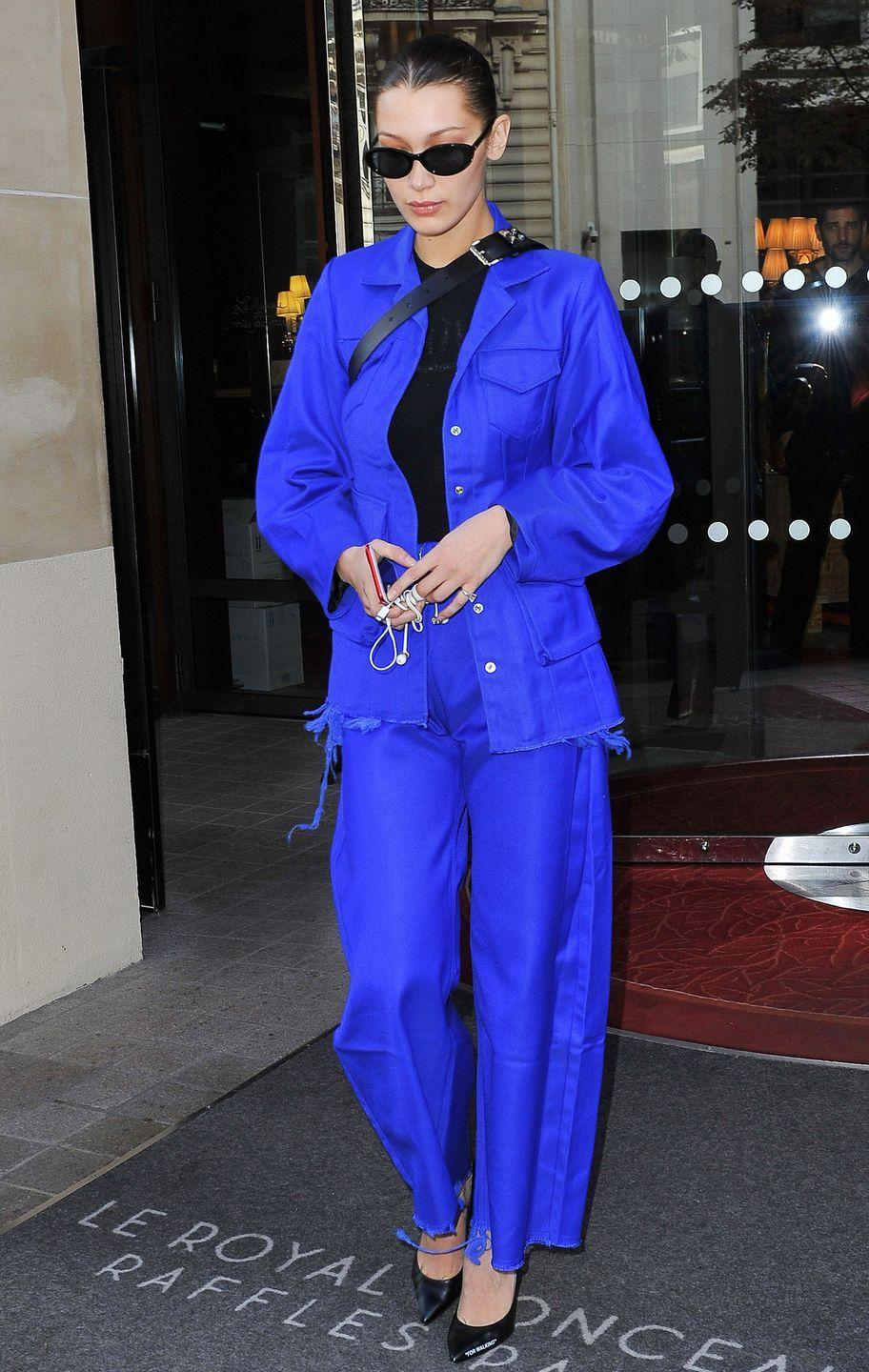"""<p>In a cobalt blue jacket and matching trousers with frayed hems, black top, Roberi & Fraud sunglasses, and Off-White """"For Walking"""" pumps while out in Paris.</p>"""