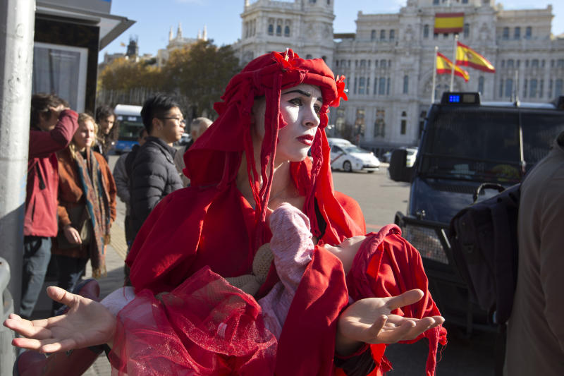 "An activist takes part in a protest at the Cibeles fountain during a protest performance in Madrid, Spain, Tuesday, Dec. 3, 2019. Some 20 activists from the international group called Extinction Rebellion cut off traffic in central Madrid and staged a brief theatrical performance to protest the climate crisis. The activists held up a banner in Russian that read ""Climate Crisis. To speak the truth. To take action immediately."" Some 10 others dressed in red robes and with their faces whitened to symbolize the human species' peril danced briefly before police moved in to end the protest. (AP Photo/Paul White)"