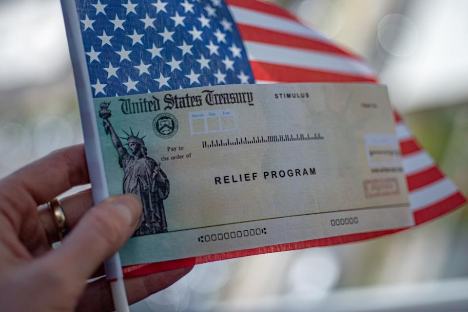 COVID-19 economic Stimulus check in female hand on blurred USA flag background. Relief program concept.