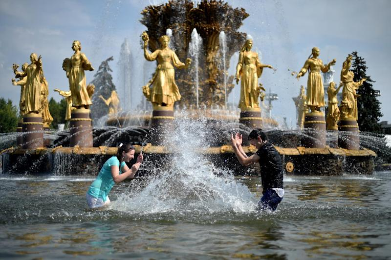 Youngsters splash water on a hot summer's day while standing in the pool of famous 'Druzhba narodov' ('Friendship of nations') fountain at the VDNKh, a public park and exhibition space in Moscow, on July 30, 2014
