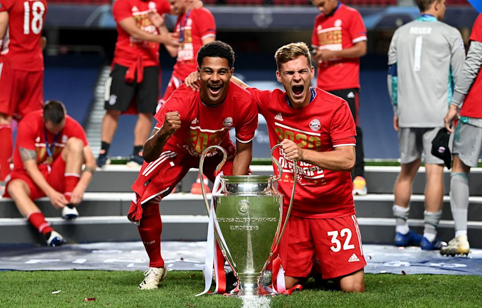 LISBON, PORTUGAL - AUGUST 23: Serge Gnabry and Joshua Kimmich of FC Bayern Munich celebrate with the UEFA Champions League Trophy following their team's victory in the UEFA Champions League Final match between Paris Saint-Germain and Bayern Munich at Estadio do Sport Lisboa e Benfica on August 23, 2020 in Lisbon, Portugal. (Photo by Michael Regan - UEFA/UEFA via Getty Images)