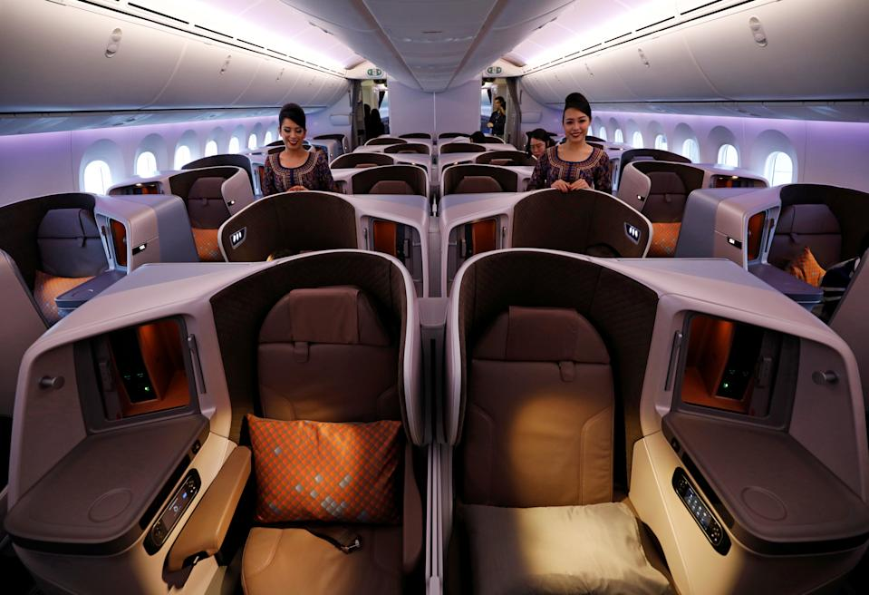 Cabin crew pose in the business class cabin of Singapore Airlines' first Boeing 787-10 Dreamliner at Singapore's Changi Airport March 28, 2018. REUTERS/Edgar Su