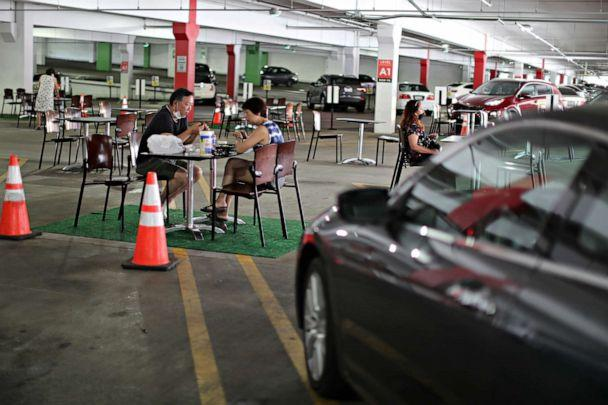 PHOTO: People eat lunch in a dining area set up in the Glendale Galleria mall parking garage in Glendale, Calif., July 31, 2020. (Lucy Nicholson/Reuters)