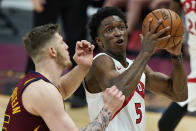 Toronto Raptors' Stanley Johnson, right, drives to the basket against Cleveland Cavaliers Isaiah Hartenstein in the second half of an NBA basketball game, Saturday, April 10, 2021, in Cleveland. (AP Photo/Tony Dejak)