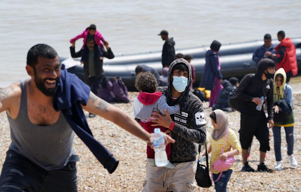 People thought to be migrants make their way up the beach after arriving on a small boat at Dungeness in Kent. Picture date: Monday July 19, 2021. (PA Wire)