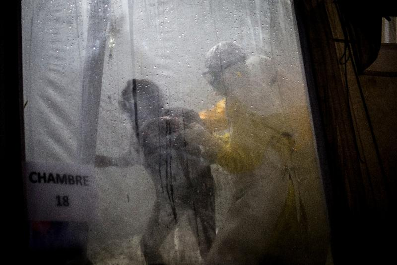 Health workers assist a possible Ebola patient into her bed at an Ebola treatment center supported by the Doctors Without Borders group in Butembo, in the Democratic Republic of the Congo (AFP Photo/John WESSELS)