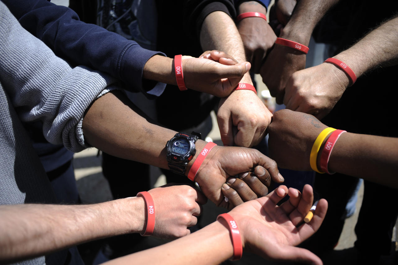 Job seekers show their wristbands, signifying which spot they are in line, as they wait in front of the training offices of Local Union 46, the union representing metallic lathers and reinforcing ironworkers, in the Queens borough of New York, April 29, 2012. About 500 people have been camping in front of the offices for a week after the State Department of Labor and the union announced they were looking to hire iron and wood apprentices for 50 positions.  On Monday the first 500 people, who were given wristbands, will be given applications for the 50 positions. REUTERS/Keith Bedford  (UNITED STATES - Tags: BUSINESS EMPLOYMENT)
