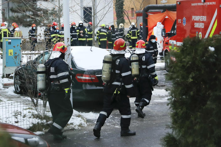 Firefighters walk at the the Matei Bals hospital compound after a fire broke out in one of its buildings in Bucharest, Romania, Friday, Jan. 29, 2021. A fire early Friday at a key hospital in Bucharest that also treats COVID-19 patients killed four people, authorities said. (AP Photo/Vadim Ghirda)
