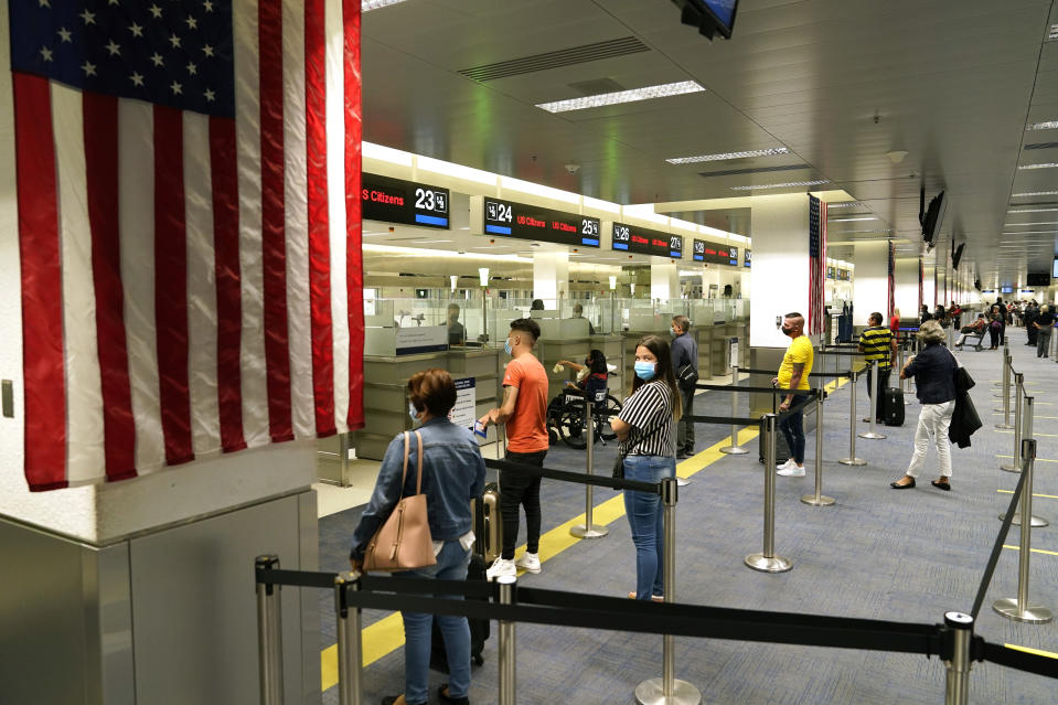 International passengers arrive at Miami international Airport where they are screened by U.S. Customs and Border Protection (CBP) using facial biometrics to automate manual document checks required for admission into the U.S. Friday, Nov. 20, 2020, in Miami. Miami International Airport is the latest airport to provide Simplified Arrival airport-wide. Rising U.S. coronavirus cases, a new round of state lockdowns and public health guidance discouraging trips are dampening enthusiasm for what is usually the biggest travel period of the year. (AP Photo/Lynne Sladky)