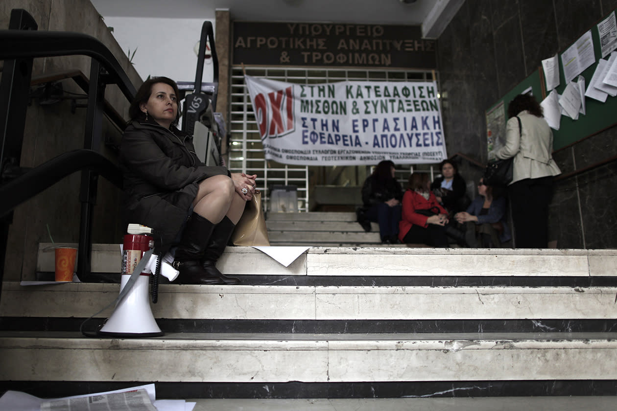 Agriculture ministry workers are seen at the entrance to the ministry headquarters in Athens, which was occupied by protesting employees.