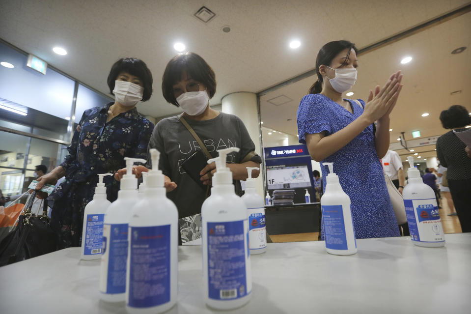 Christians wearing face masks to help protect against the spread of the new coronavirus use hand sanitizer before attending a service at the Yoido Full Gospel Church in Seoul, South Korea, Sunday, July 5, 2020. (AP Photo/Ahn Young-joon)