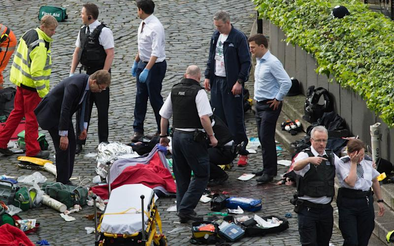 Tobias Ellwood (left) stands amongst the emergency services at the scene  - Credit: Stefan Rousseau/PA