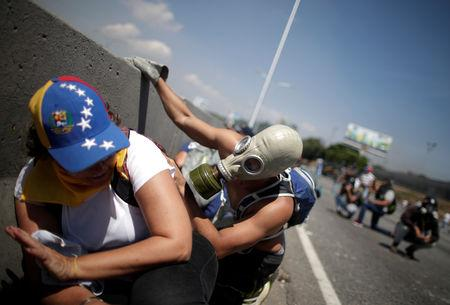 "Opposition demonstrators take cover near the Generalisimo Francisco de Miranda Airbase ""La Carlota"" in Caracas"