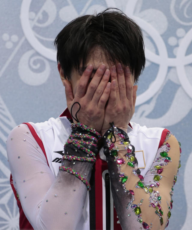 Yuzuru Hanyu of Japan reacts as he sits in the results area after the men's free skate figure skating final at the Iceberg Skating Palace at the 2014 Winter Olympics, Friday, Feb. 14, 2014, in Sochi, Russia. (AP Photo/Ivan Sekretarev)