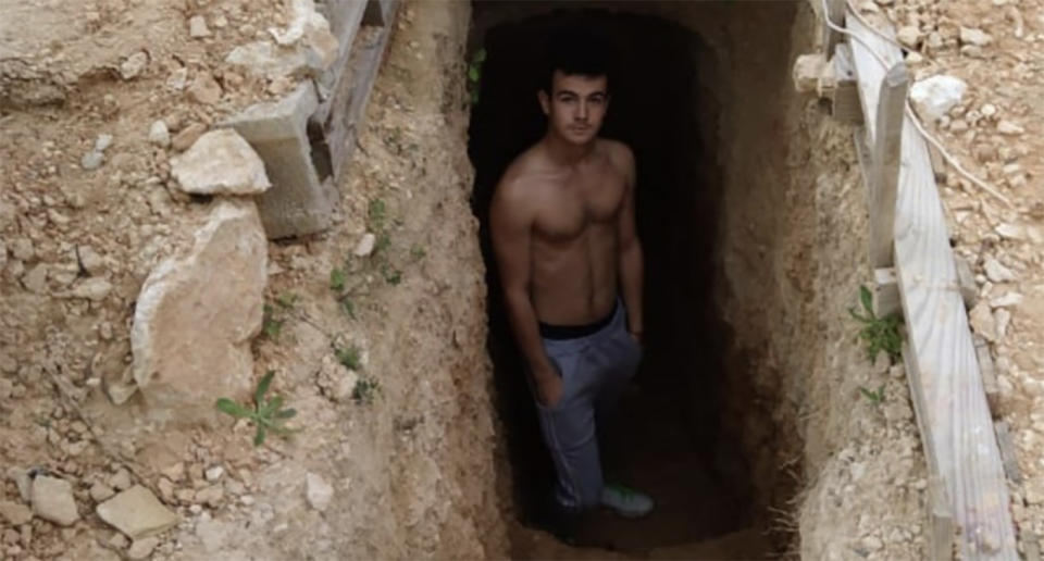 Andres Canto pictured in a hole underneath his house.