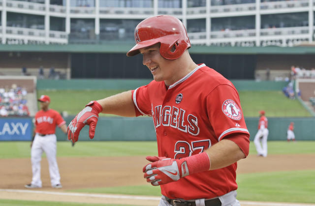 Los Angeles Angels' Mike Trout smiles as he runs back to the dugout after a sacrifice fly that scored teammate Erick Aybar during the first inning of a baseball game against the Texas Rangers Saturday, Sept. 28, 2013, in Arlington, Texas. (AP Photo/LM Otero)