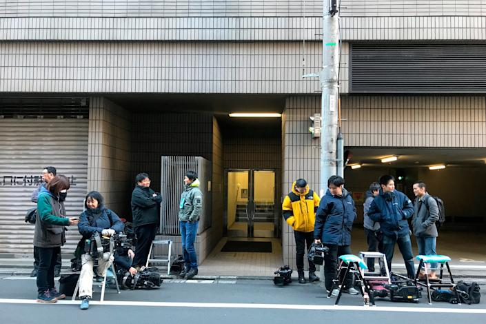 Journalists stake out at the back entrance of a building which houses an office of Junichiro Hironaka, a lawyer for Nissan's former Chairman Carlos Ghosn, in Tokyo Tuesday, Dec. 31, 2019. Ghosn, who is awaiting trial in Japan on charges of financial misconduct, has arrived in Beirut, a close friend said Monday. He apparently jumped bail. It was not clear how Ghosn, who is of Lebanese origin and holds French and Lebanese passports, left Japan where he was under surveillance and is expected to face trial in April 2020. (AP Photo/Richard Colombo)