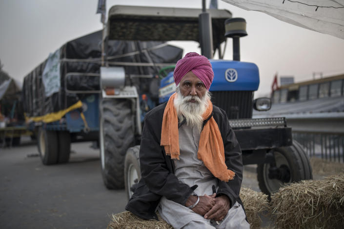 Farmer Atma Singh, 62, poses for a photograph as next to his tractor parked on a highway during a protest at the Delhi-Haryana state border, India, Wednesday, Dec. 2, 2020. The farmers are protesting new laws they say will result in their exploitation by corporations, eventually rendering them landless. Now, they are blocking highways, unwilling to withdraw and threatening to besiege the capital if their demands aren't met. (AP Photo/Altaf Qadri)