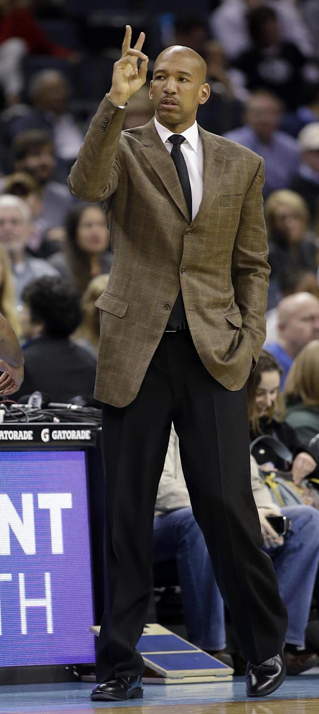 New Orleans Pelicans coach Monty Williams makes a call against the Charlotte Bobcats during the first half of an NBA basketball game in Charlotte, N.C., Friday, Feb. 21, 2014. (AP Photo/Bob Leverone)