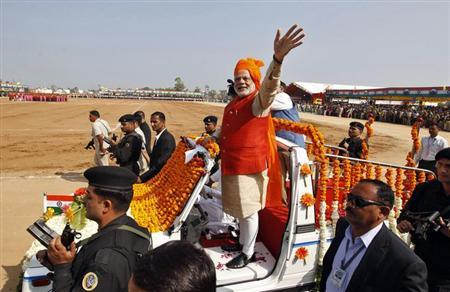 Narendra Modi waves after hoisting an Indian national flag during the Republic Day celebrations at Himmatnagar town, about 69 km east from Ahmedabad, January 26, 2014. REUTERS/Amit Dave/Files