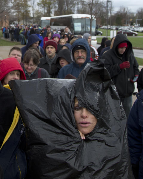 Justine Ovsenik of Willoughby Hills, Ohio, struggles to stay warm with the help of a trash bag as she waits in line to enter Mentor High School to hear President Barack Obama speak at a campaign event, Saturday, Nov. 3, 2012, in Mentor, Ohio, before he travels to Milwaukee for another Campaign event. (AP Photo/Carolyn Kaster)