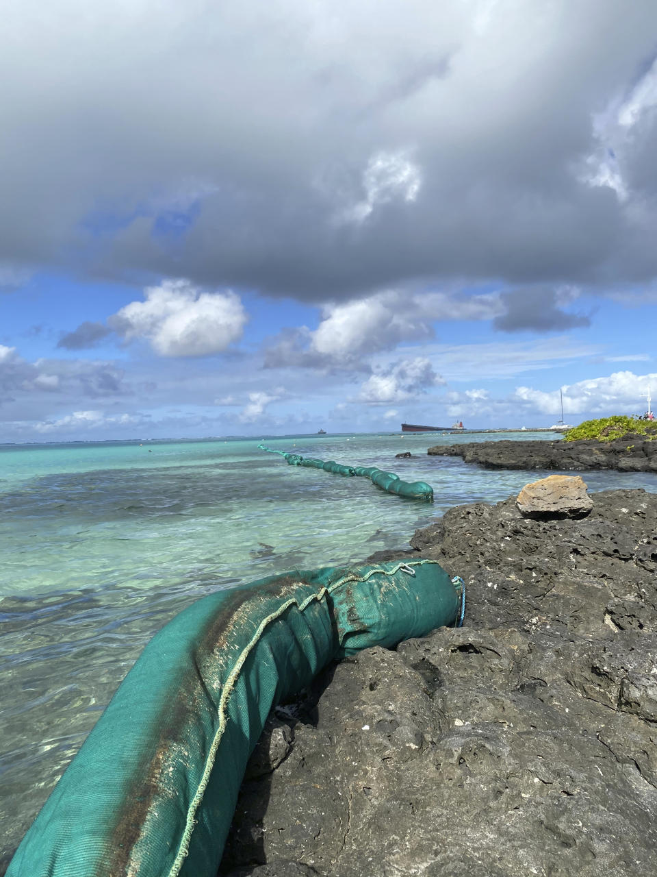 """In this photo provided by Grégoire Rouxel a ship, top right, off shore that ran aground is leaking fuel in the ocean, Friday, Aug. 7, 2020, in Mauritius. The Indian Ocean island of Mauritius has declared a """"state of environmental emergency"""" after a Japanese-owned ship that ran aground offshore days ago began spilling tons of fuel. Prime Minister Pravind Jugnauth announced the development late Friday, Aug. 7, as satellite images showed a dark slick spreading near environmental areas the government called """"very sensitive."""" (@gregrouxel via AP)"""