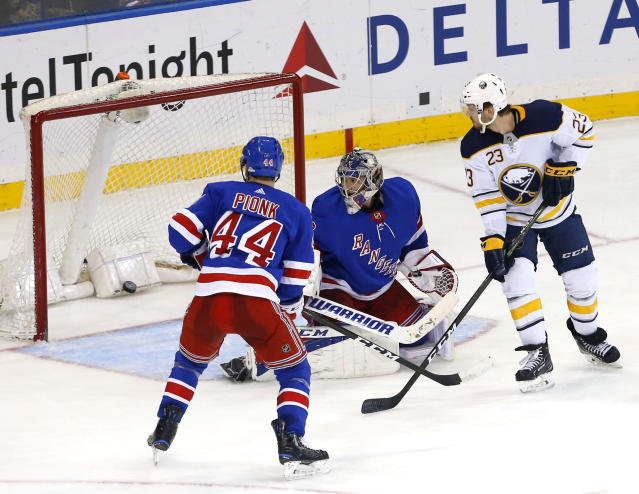 Buffalo Sabres center Sam Reinhart (23) scores a goal against New York Rangers goaltender Alexandar Georgiev (40) and defenseman Neal Pionk (44) during third period of an NHL hockey game, Saturday, March 24, 2018, in New York. (AP Photo/Noah K. Murray)