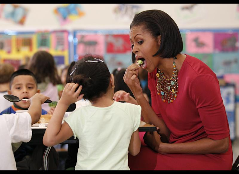 First lady Michelle Obama eats a piece of broccoli as she sits down to eat with students during their visit to New Hampshire Elementary School, Mexican First Lady Margarita Zavala, not shown, Wednesday, May 19, 2010, in Silver Spring, Md. The school, which was awarded the USDA's Healthier US School Challenge Silver Award in 2009, serves more than 400 Pre-K, Head Start, first and second grade students, many who come from Central America, South America, and other countries. (AP Photo/Pablo Martinez Monsivais)
