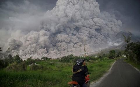 <span>An Indonesian man takes picture of Mount Sinabung volcano as it spews thick volcanic ash into the air in Karo, North Sumatra, on February 19, 2018</span> <span>Credit: ENDRO RUSHARYANTO/AFP </span>