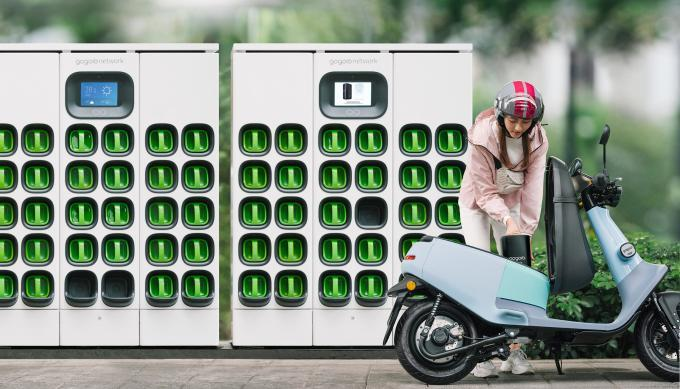 A photograph of a woman standing next to a scooter in front of a Gogoro battery swapping station