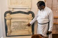 A pastor shows a memorial tablet for Christopher Biden, born in 1789, at St George's Cathedral in Chennai