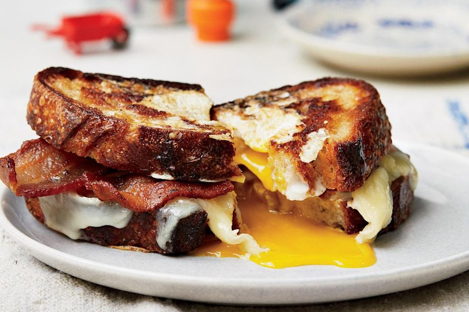 """This breakfast sandwich is one of our favorite comfort food recipes, and we absolutely wouldn't blame you if you wanted to make it for a quick weeknight dinner. Step one: cut holes in two pieces of sourdough. Step two: fry eggs in those holes. Step three: slap them together with crispy bacon, melty cheddar, and plenty of hot sauce. <a href=""""https://www.epicurious.com/recipes/food/views/egg-in-a-hole-sandwich-with-bacon-and-cheddar?mbid=synd_yahoo_rss"""" rel=""""nofollow noopener"""" target=""""_blank"""" data-ylk=""""slk:See recipe."""" class=""""link rapid-noclick-resp"""">See recipe.</a>"""