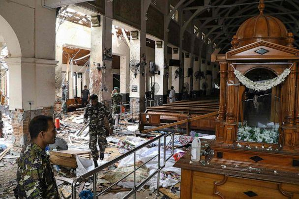 PHOTO: Sri Lankan security personnel walk past dead bodies covered with blankets amid blast debris at St. Anthony's Shrine following an explosion in the church in Kochchikade in Colombo, April 21, 2019. (Ishara S. Kodikara/AFP/Getty Images)