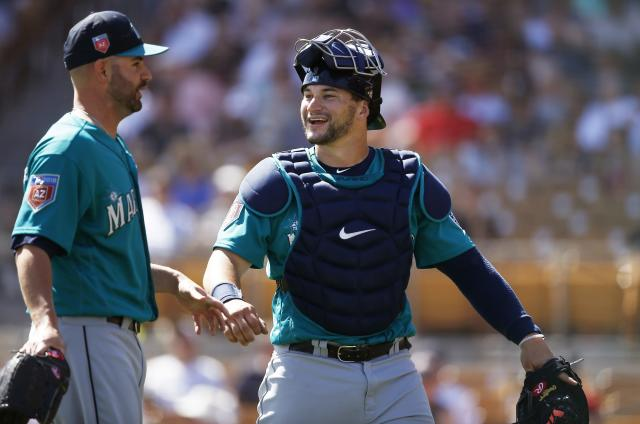 Seattle Mariners catcher Mike Zunino, right, smiles as he talks with relief pitcher Marc Rzepczynski, left, during the fifth inning of a spring training baseball game against the Chicago White Sox, Friday, March 23, 2018, in Glendale, Ariz. (AP Photo/Ross D. Franklin)
